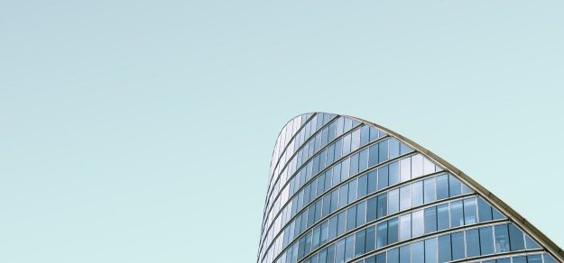 Photo by Simone Hutsch, round building, made out of glas in front of a light blue sky.