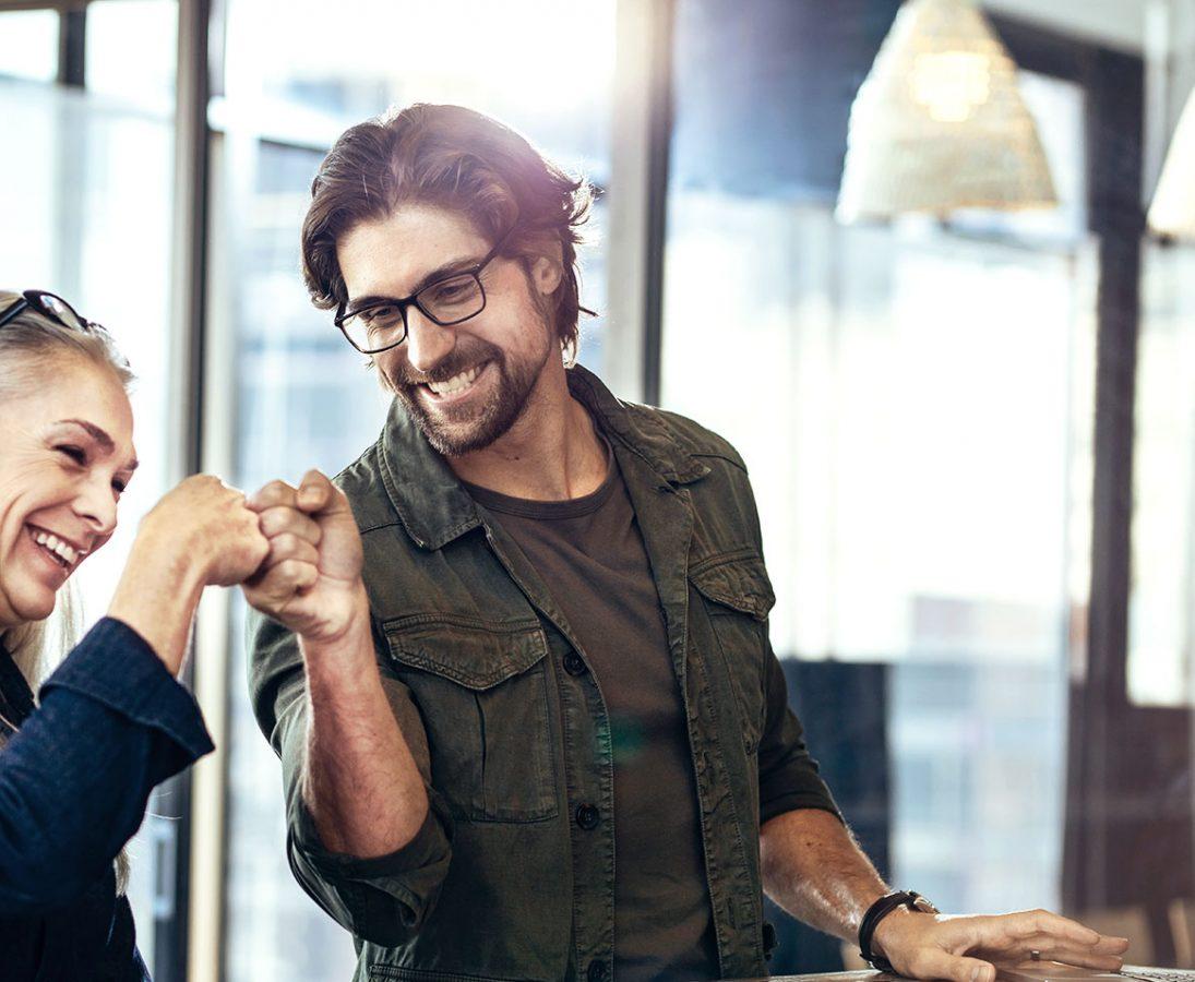 Eine Frau und ein Mann machen ein Fistbump.