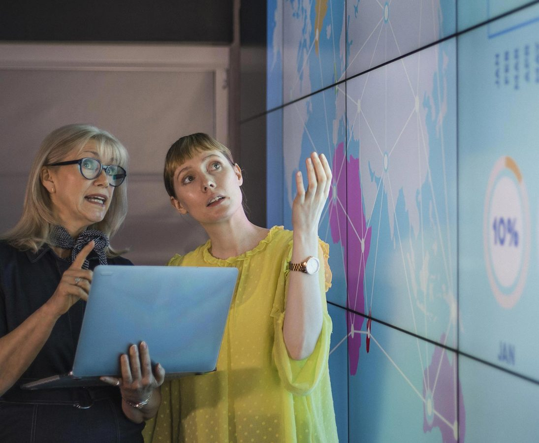 Zwei Frauen diskutieren an einer interaktiven Mediawand.