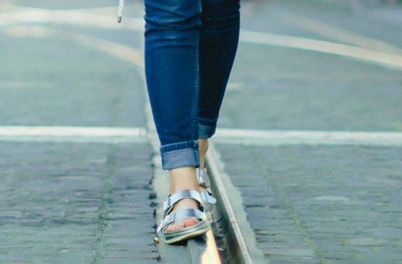 Eine Frau läuft in silbernen Hausschuhen und blauer Jeans auf einem Straßenbahngleis.