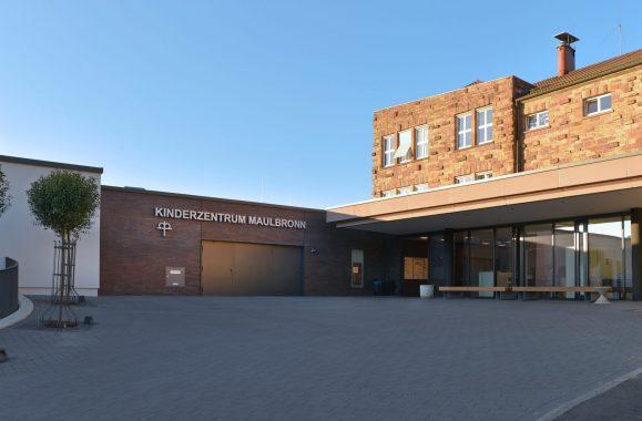 Das Kinderzentrum Maulbronn. Ein braunes Steingebäude mit Palmen vor dem Eingang.