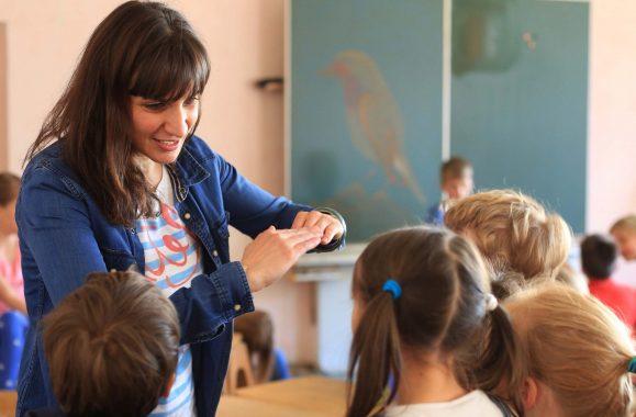 Eine Lehrerin spricht mit Kindern in einem Klassenzimmer. Im Hintergrund befindet sich eine Tafel an der Wand.