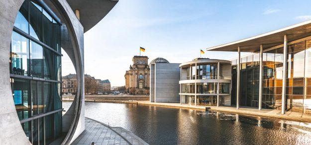 Das Regierungsviertel in Berlin. Ein Wasserkanal umgeben von Beton und Glasbauten.