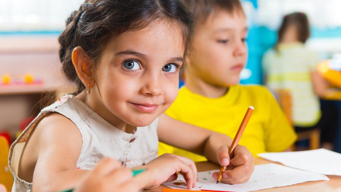 Ein Kind schreibt mit einem Bleistift auf ein Blatt Papier, während es direkt in die Kamera blickt.