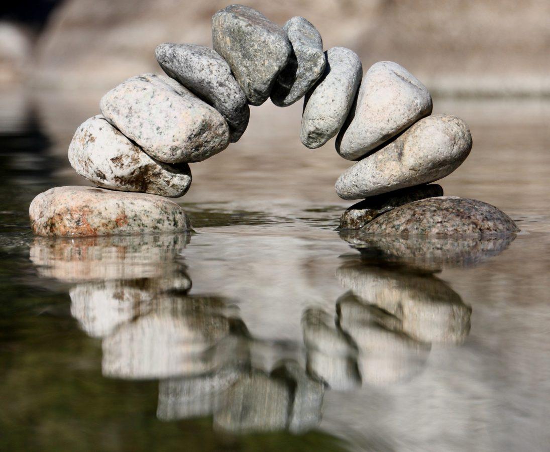 zu einem Bogen aufgeschichtete Steine die im Wasser stehen und sich darin spiegeln.