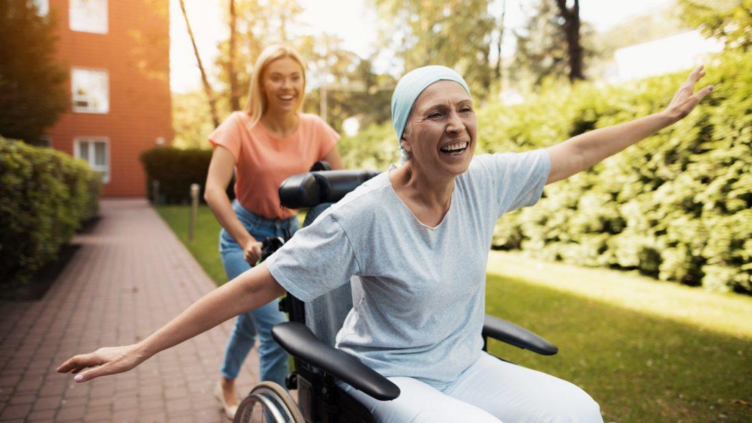 Eine Frau im Rollstuhl streckt ihre Hände aus während sie von einer jungen Frau schnell geschoben wird.