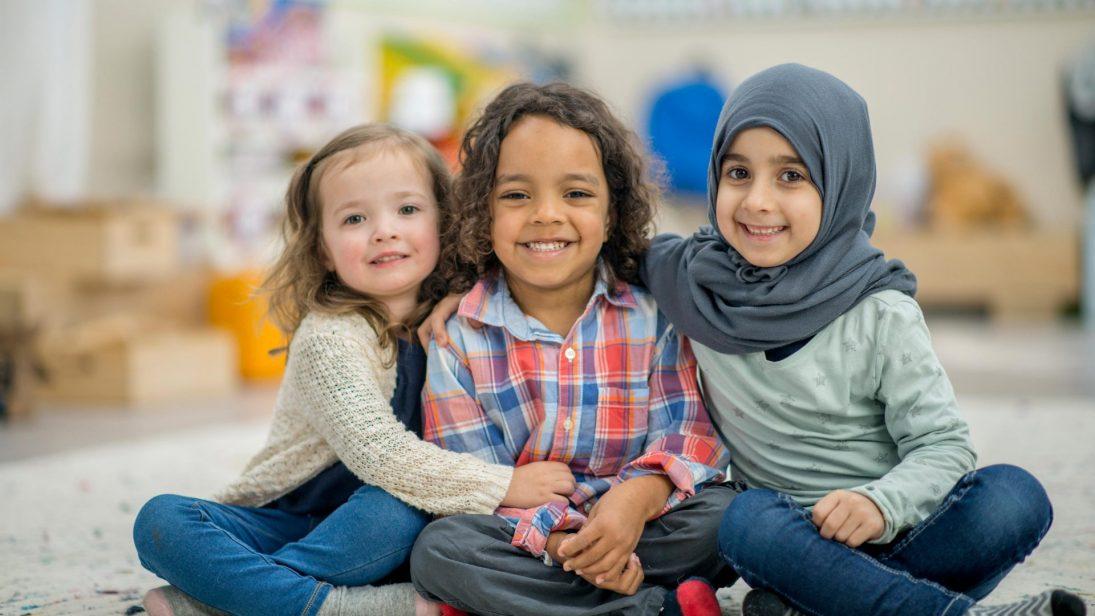 Drei Kinder unterschiedlicher Herkunft sitzen zusammen am Boden und armen sich glücklich.