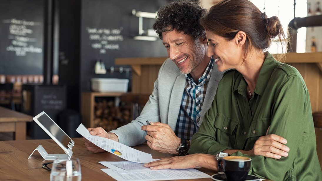Eine Frau sitzt zusammen mit einem Mann an einem Tisch. Sie lächeln freundlich und schauen sich Papiere an.